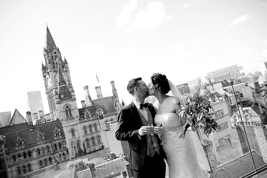 Black and white landscape of bride and groom kissing